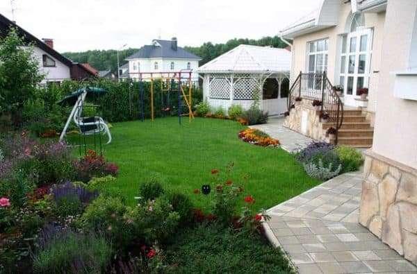 Двор частного дома с игровой зоной и качелей