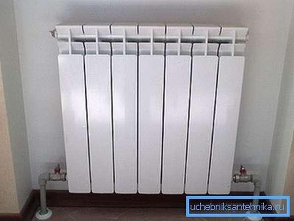 Биметаллический радиатор с нижним подключением в интерьере комнаты.