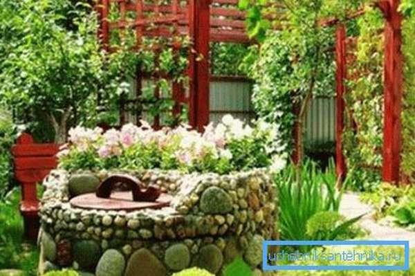 Колодец, декорированный камнями и цветами