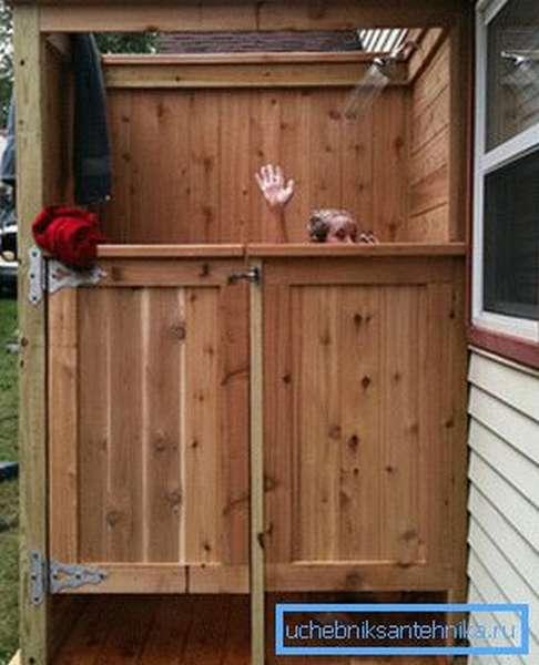 Летний душ из дерева для дачи можно пристроить к дому и подключить к общим коммуникациям.
