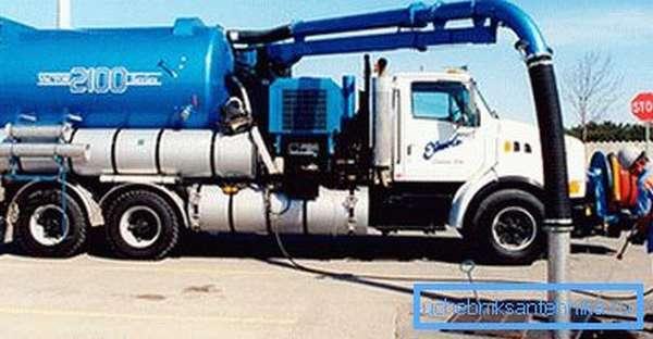 Любительское фото большой промышленной машины на автомобильном шасси в момент произведения очистки канализационной системы