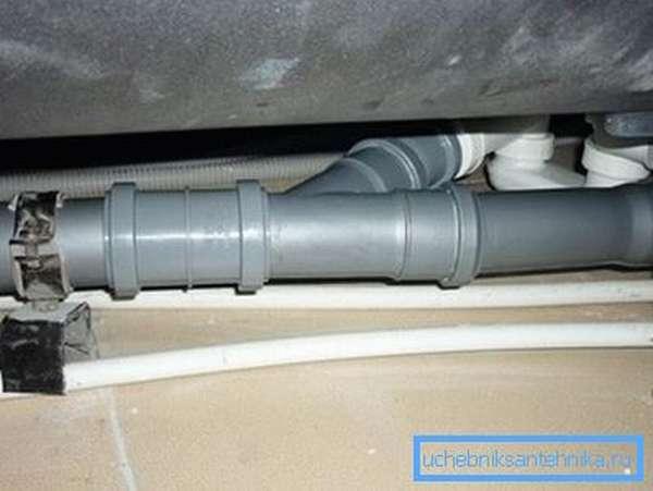 Любительское фото системы канализационных труб, расположенных под ванной