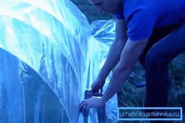 Монтаж целлофановой плёнки на парниковый скелет