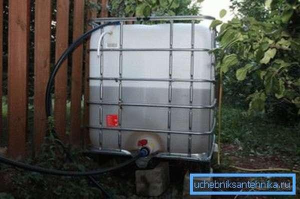 На фото - емкость с краном с водой на участке