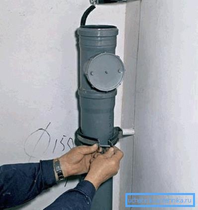 На фото фиксация трубы хомутом.