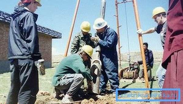 На фото группа специалистов занимается бурением скважины