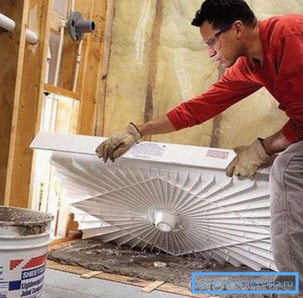 На фото – низкий поддон в процессе укладки на подушку из цемента