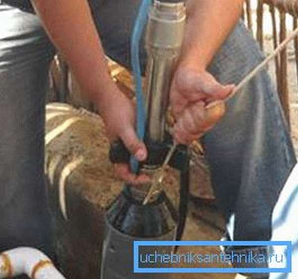 На фото показан процесс погружения насоса в скважину.