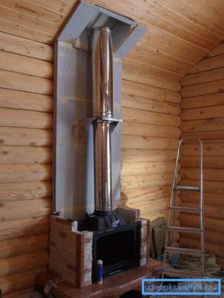На фото - пример установки стальной трубы в деревянном коттедже