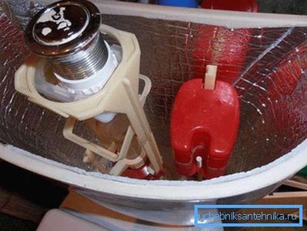 На фото проблема излишней влаги на поверхности бачка устранена с помощью фиксирования на внутренних стенках прибора теплоизоляционного материала