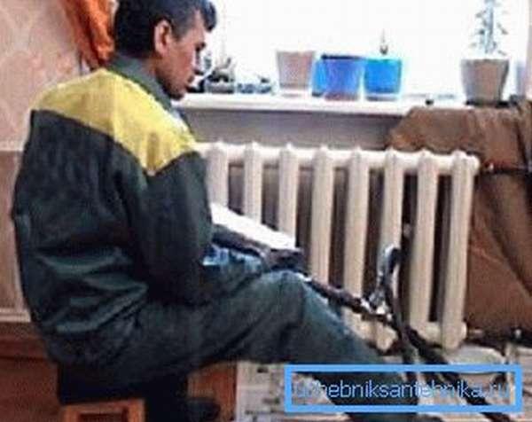 На фото сантехником производится промывка радиаторов отопления в квартире