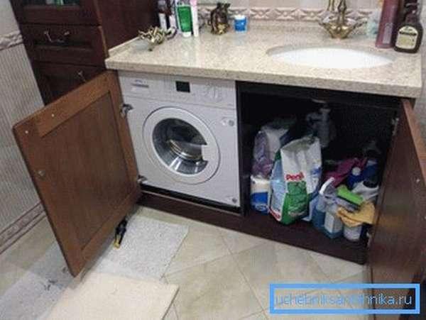 На фото – вариант размещения стиральной машины под мойкой в ванной комнате