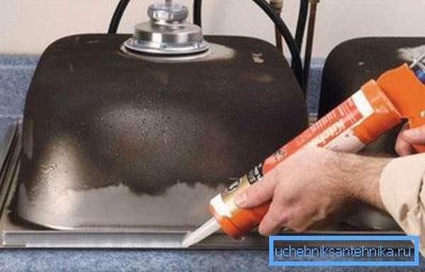 Нанесение силикона на внутреннюю часть накладной мойки из нержавеющей стали для кухни перед монтажом в столешницу