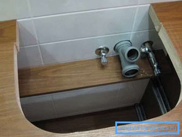 Отверстие под раковину в столешнице тумбы с установленными вводами систем коммуникаций