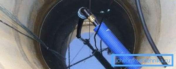 Пробитое отверстие для трубы в колодце и подсоединенная труба.
