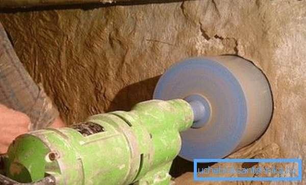 Процесс пробивания отверстия под ввод водопровода в дом под фундаментом.