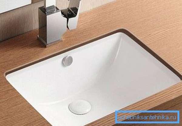 Раковина - встроенная в столешницу в ванной, выглядит стильно и современно.