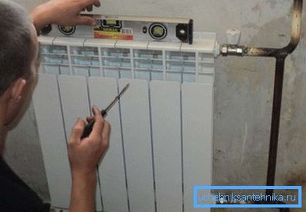 Выравнивание отопительной батареи с помощью водяного уровня