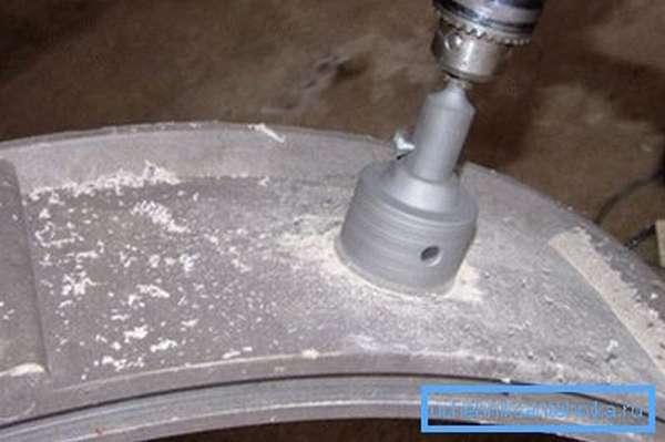 Вырезаем отверстие для трубы в бетонном кольце.